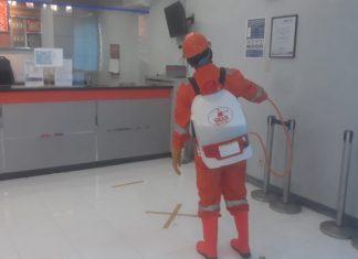 Petugas Sedang Menyemprotkan Disinfektan ke kantor BRI
